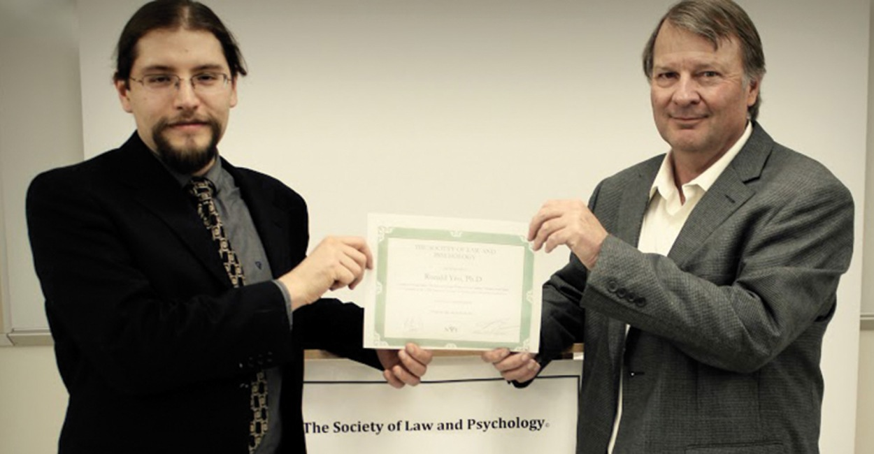 Gabriel Roybal presenting Dr. Ron Yeo with honorary SLP membership certificate.