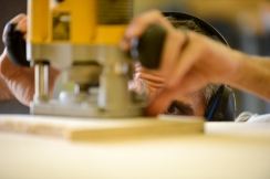 Marty Bonacci adjusts a router for finishing the guitar bodies he manufactures at Makerspace.